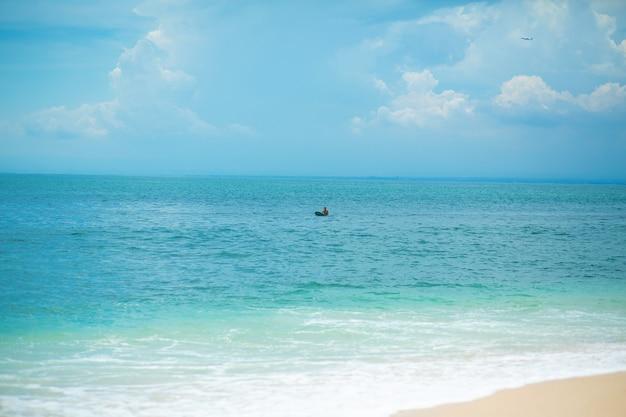 Il ragazzo sta nuotando sulla tavola da surf nell'oceano. stile di vita sano e attivo nella vocazione estiva.