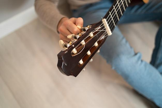 Il ragazzo sta accordando la chitarra. primo piano di una tastiera di chitarra. l'uomo torce i piroli di accordatura al collo della chitarra.
