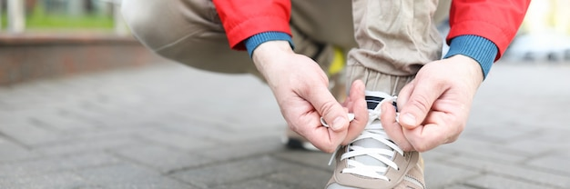 Il ragazzo con la giacca sta legando i lacci degli stivali