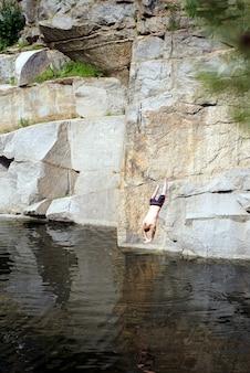 Il ragazzo salta dalla roccia in acqua in un canyon. persona impavida. grande altezza e lago profondo.