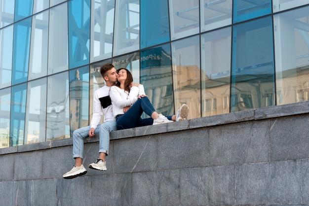 Ragazzo bacia la sua ragazza. data della giovane coppia in città. urbano. coppia di innamorati che riposano vicino a un edificio moderno.