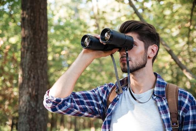 Ragazzo che guarda il binocolo nella foresta