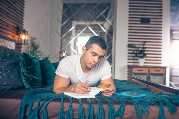 Ragazzo sdraiato su un letto con una carta di credito in mano, copiando il suo numero nel taccuino.