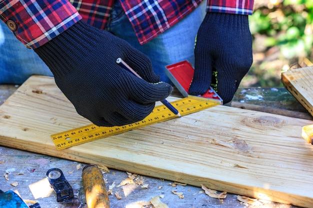 Il ragazzo fa un disegno con un righello da costruzione su assi di legno