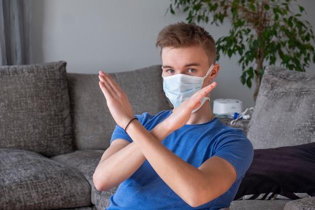 Ragazzo in una maschera medica con le braccia incrociate, mostrando stop coronavirus. l'uomo si tiene per mano davanti al viso