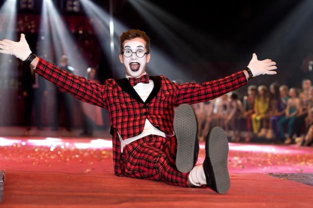 Il mimo del ragazzo in un vestito si siede sul pavimento nel circo. l'artista comico sul palco diverte il pubblico