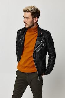 Ragazzo in maglione arancione e giacca di pelle che guarda verso il biondo
