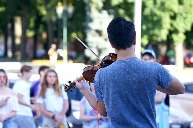 Guy suona il violino per la gente di strada