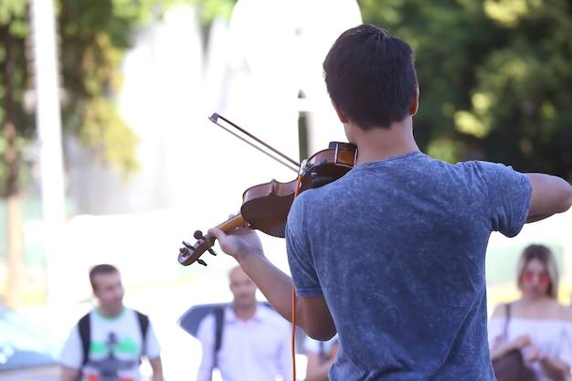 Ragazzo suona il violino per la gente di strada