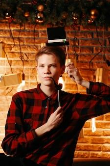 Ragazzo in posa con cappello a cilindro e cabina fotografica tubo attribuisce gentiluomo in camicia a quadri sul muro di mattoni bac...