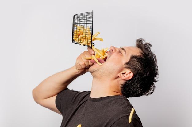 Il ragazzo mette le patatine fritte in bocca sul muro bianco