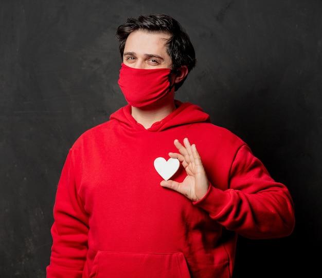 Ragazzo in felpa rossa tenere il cuore sulla parete scura