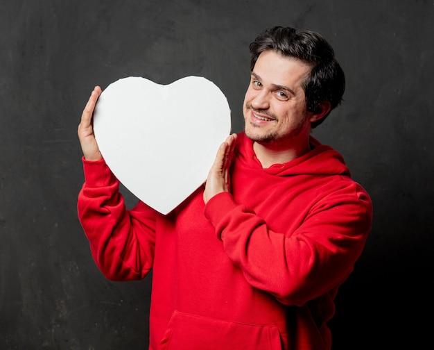 Ragazzo in felpa rossa tenere cornice a forma di cuore sulla parete scura