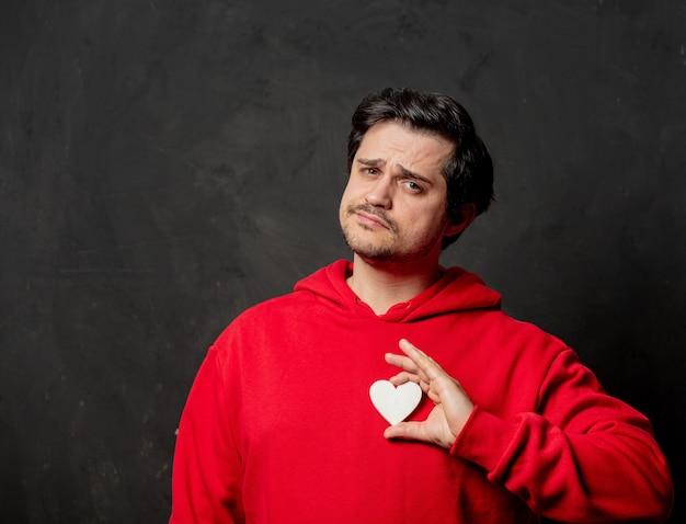 Ragazzo in felpa rossa tenere a forma di piccolo cuore sul muro scuro