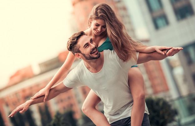 Ragazzo rotola ragazza sulla schiena e la guarda con un sorriso. le coppie allegre si divertono insieme.