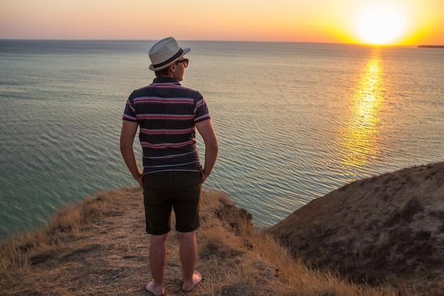Un ragazzo in pantaloncini, maglietta a righe, cappello e occhiali da sole in piedi su un'alta scogliera in riva al mare o all'oceano.
