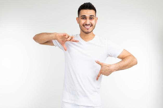 Guy mostra un modello sulla sua maglietta bianca su uno sfondo bianco