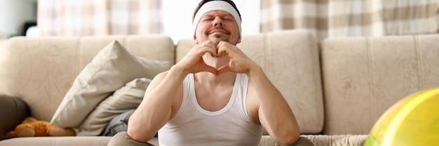 Guy si siede a casa tappeto medita e mostra il cuore