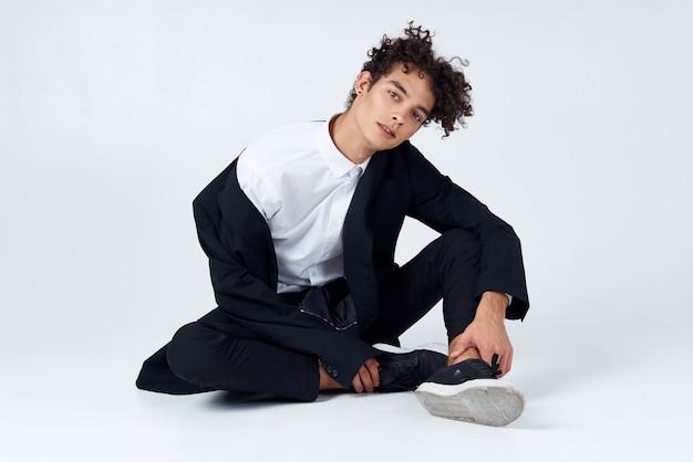 Ragazzo seduto sul pavimento capelli ricci vestito stile moderno isolato