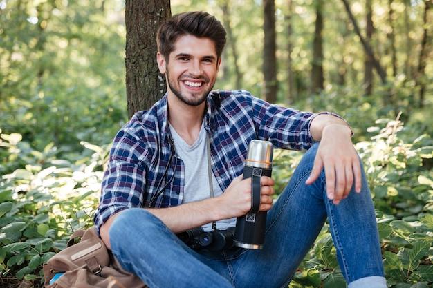 Ragazzo seduto con thermos nella foresta