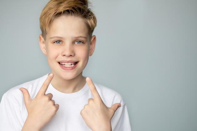 Il ragazzo sorride e mostra i suoi denti frastagliati con la sua mano medicina dentale e assistenza sanitaria