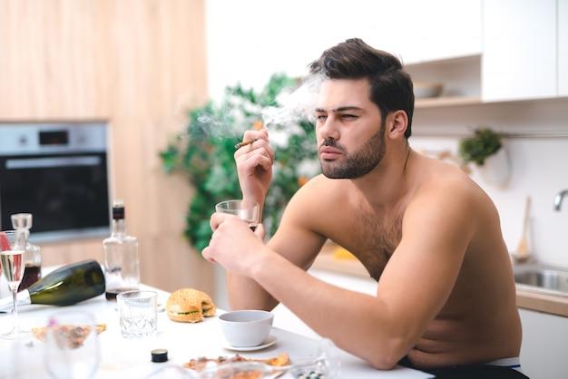 Ragazzo che fuma e soffre di postumi di una sbornia.