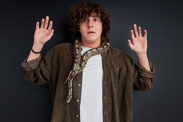 Guy stare con le braccia aperte spaventato da python su di lui, isolato su sfondo nero. concetto di persone e animali