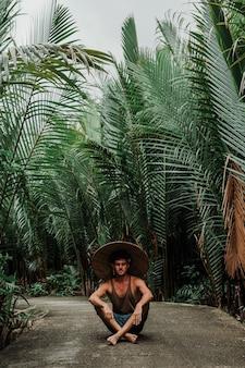 Ragazzo in un cappello di paglia in ambiente tropicale