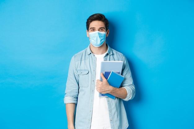 Ragazzo studente in maschera medica che sembra felice, tenendo i taccuini, in piedi sul muro blu