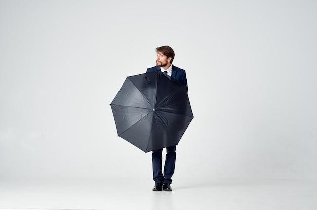 Ragazzo in abito con un ombrello in mano