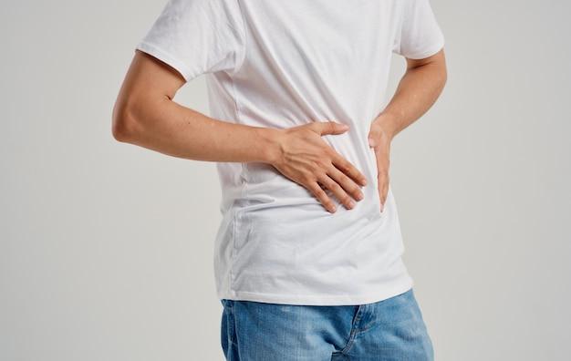 Ragazzo in una maglietta e jeans tocca le mani vicino all'appendicite problemi di stomaco dolore addome