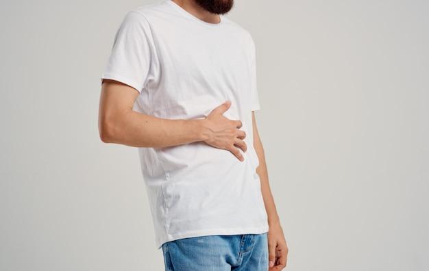 Ragazzo in una t-shirt e jeans tocca le mani vicino all'appendicite problemi di stomaco dolore addome