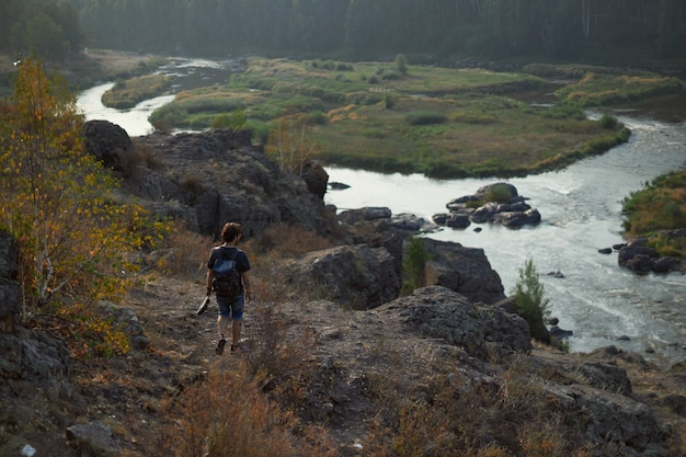 Il viaggiatore del tipo cammina nelle montagne vicino al fiume in tempo soleggiato caldo il concetto di giovent...