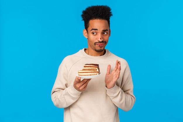 Guy ha provato a mordere la torta non gli piaceva il gusto. uomo afroamericano scettico dispiaciuto e non impressionato, esigente con cioccolato al naso, con dessert e scuotendo la testa in no, rifiuto, ghigno e rabbia