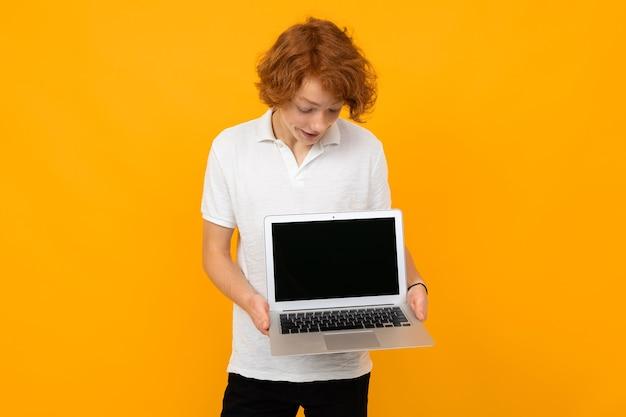 Guy in una camicia bianca mostra lo schermo di un laptop con un mockup su uno sfondo giallo.