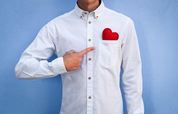 Il ragazzo con la camicia bianca punta il dito contro un san valentino rosso che ha in tasca