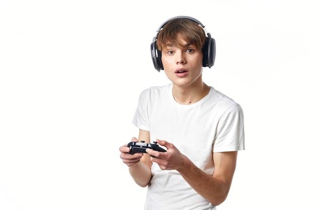 Ragazzo con una maglietta bianca in cuffia con un giocatore di tecnologia per videogiochi con joystick