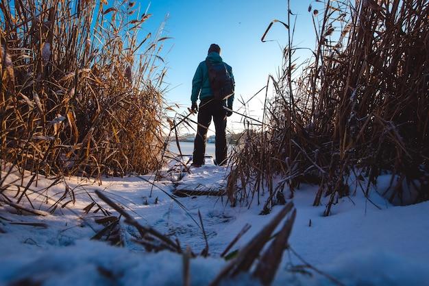 Il ragazzo con lo zaino è in piedi sul lago ghiacciato e guarda avanti.