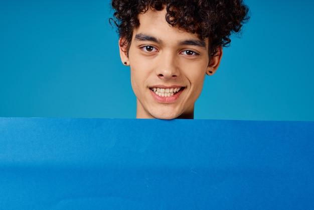 Un ragazzo con i capelli ricci con in mano un poster