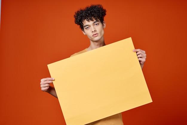 Ragazzo con i capelli ricci isola nelle mani pubblicità sfondo rosso