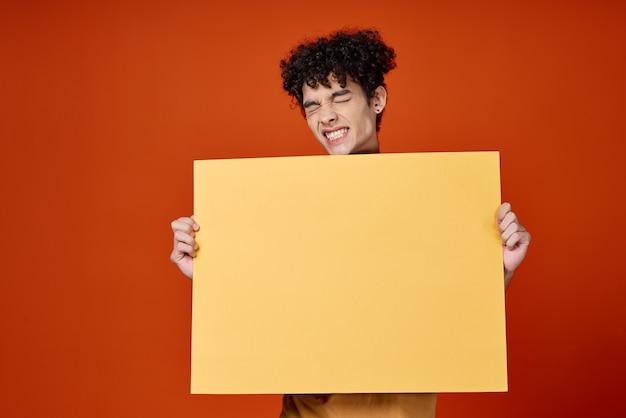 Ragazzo con capelli ricci giallo poster pubblicità sfondo rosso isolato