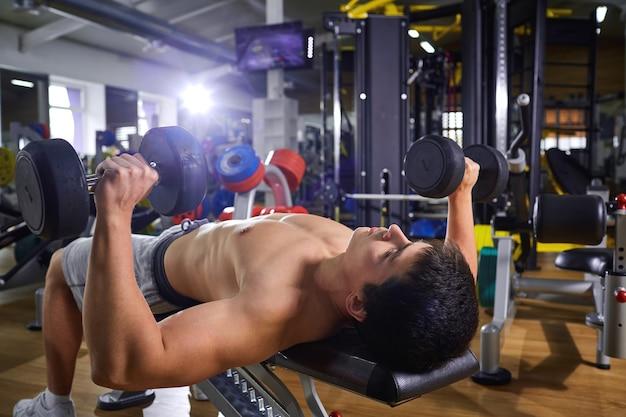 Un ragazzo con manubri sdraiato facendo esercizi in palestra