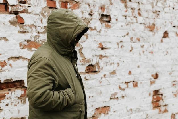 Ragazzo con un cappuccio sopra la testa, la sua faccia non è visibile. il concetto di droga, furto e criminalità. rosso con sfondo bianco retrò brickwall grunge
