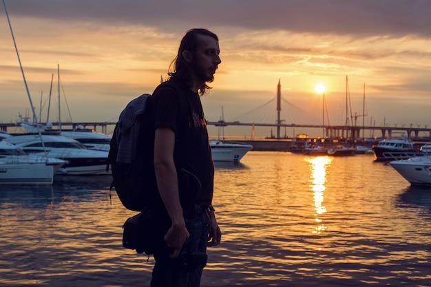 Ragazzo con i capelli lunghi in sagoma in piedi sulla spiaggia con una telecamera dove gli yacht sono ormeggiati al molo al tramonto d'estate, in lontananza, il ponte strallato