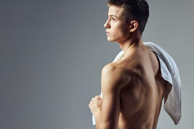 Ragazzo con un asciugamano sulle spalle torso nudo allenamento atletico sembra.