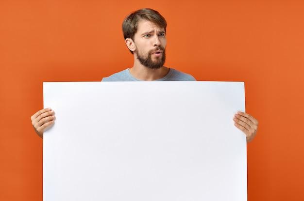 Ragazzo con carta bianca sul cartello pubblicitario mockup poster arancione