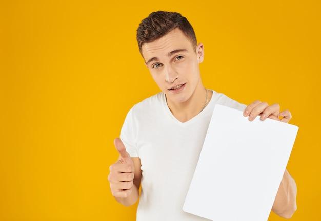 Ragazzo con foglio bianco di carta mockup giallo copia spazio.