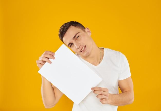 Ragazzo con bianco foglio di carta mockup parete gialla copia spazio