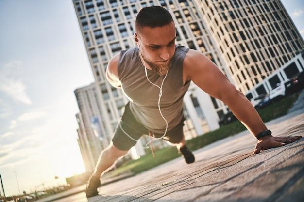Un ragazzo con le cuffie cablate nelle orecchie in una maglietta sportiva sta facendo flessioni con una mano per strada sul marciapiede, guardando attentamente davanti al pavimento