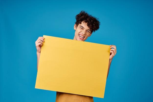 Ragazzo con poster giallo in mano